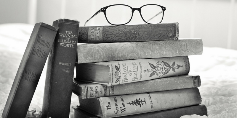 Graphic with stack of books and reading glasses
