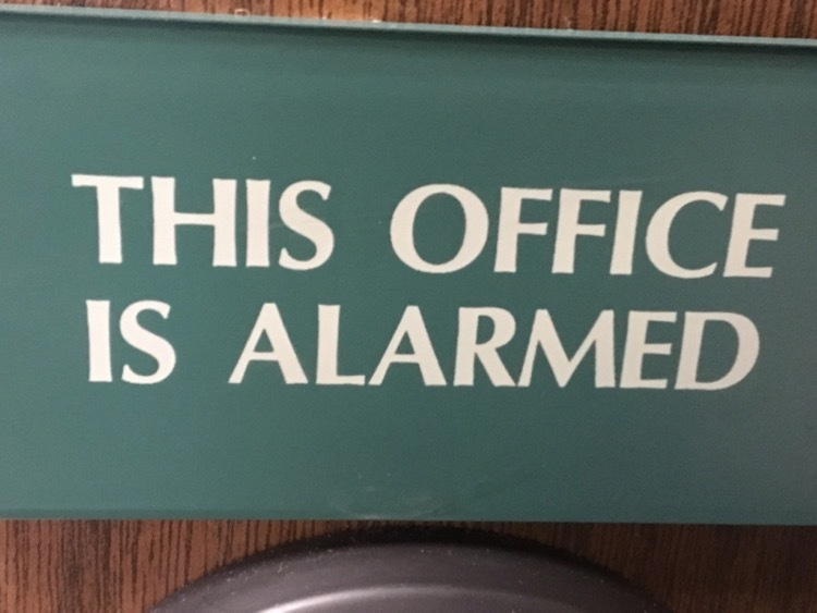 Sign that says THIS OFFICE IS ALARMED in white text on a green background