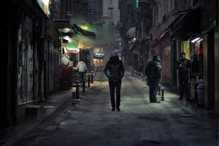 Image of a man in a hoodie walking toward viewer down a narrow street of shops