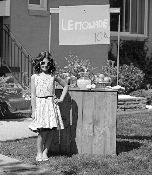 Black and white photo of a girl in front of a lemonade stand