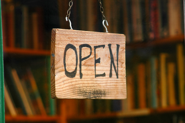 Image of bookshelves with a wooden sign that says Open