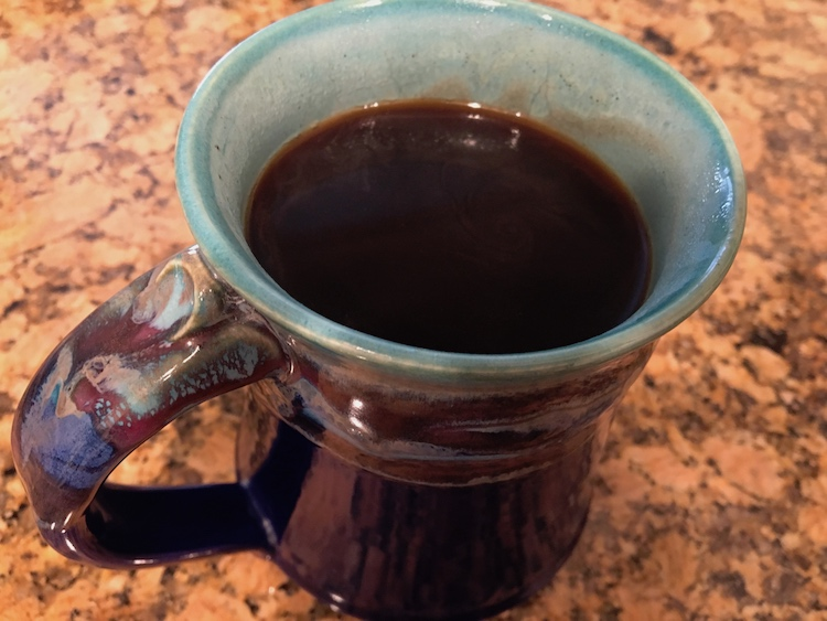 A cup of coffee in a blue and purple hand crafted mug