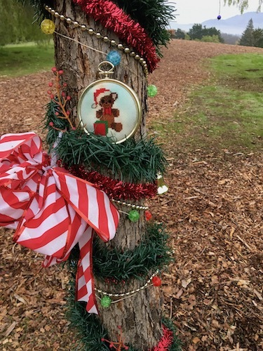 Close up of an evergreen garland and ornaments wrapped around a tree trunk