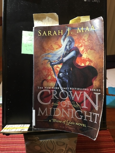 Photo of Crown of Midnight by Sarah J. Maas on a black document holder book stand