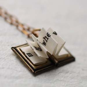 Photo of a brass book locket with folded paper to look like book pages