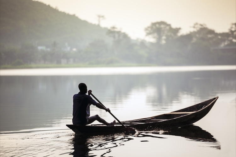 Photo of an African man riding a traditional, wooden canoe in Ghana, Africa