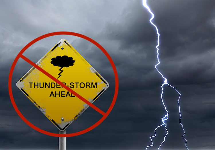 Photo of a yellow sign with Thunderstorms Ahead and a stormy sky with lightning forking toward the ground