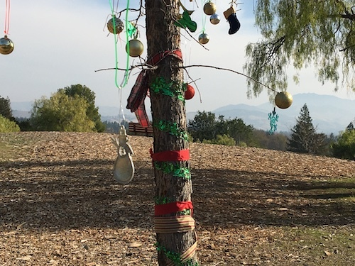 Photo of a tree trunk wrapped in red and green and decorations on branches