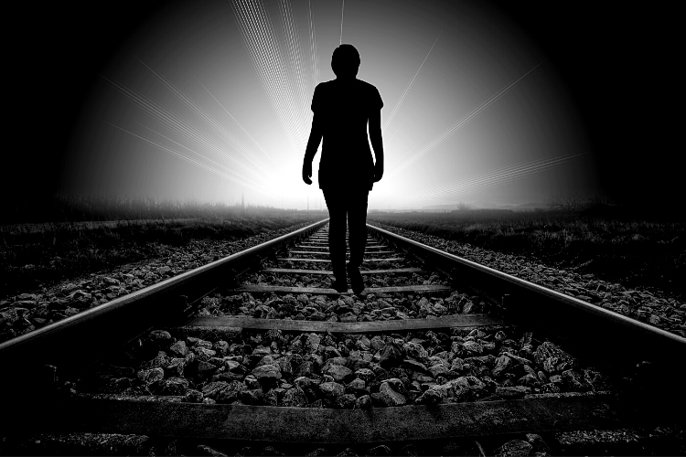 Picture of a person walking in the dark along railroad tracks toward the light