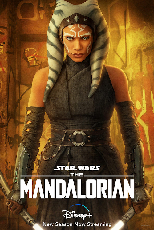 Movie poster of Ahsoka Tano looking fiercely at the viewer. She has green striped tail-like appendages instead of hair, is wearing with white face paint, grey-green battle clothes, and wielding two lightsabers, set against a gold and brown wall
