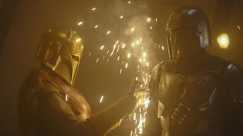 On the left, a helmeted woman with a fur cape and rust colored armor uses a welding tool on the shoulder armor of a helmeted, armored man standing on the right. Golden sparks between them from the welding.
