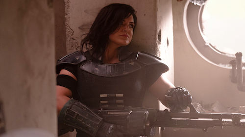 A woman wearing shoulder and forearm armor stands with her back to a square pillar. She's aiming a large machine gun off to the right. There's a round window with no glass shining white above her right shoulder.