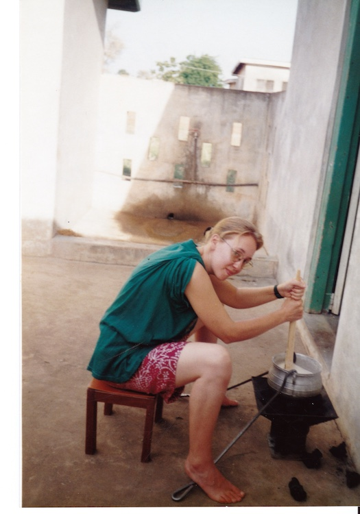 Photo of Vanessa Kier sitting on a stool in front of an unlit brazier on which sits a metal cooking pot. She is stirring the contents of the pot with a wooden spoon.