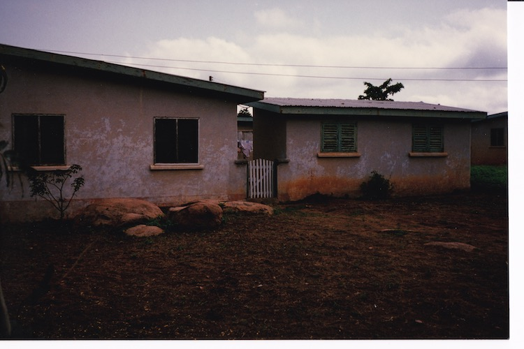 Photo of a cloudy day with a bungalow to the right, a white wooden gate then a kitchen building with pale green shutters