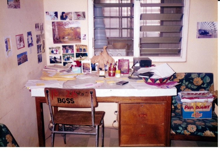 Photo of a wooden desk with two drawers on the right side in front of louvered windows looking into the dining area.