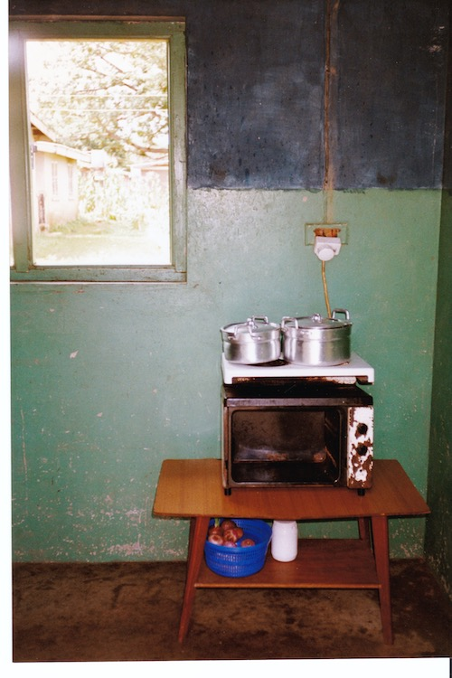 Photo of a low wooden table with a shelf beneath containing a blue plastic container holding onions. On top of the table is an old, rusted electric oven with two burners on top. Two aluminum cooking pots with handles are on the burners.