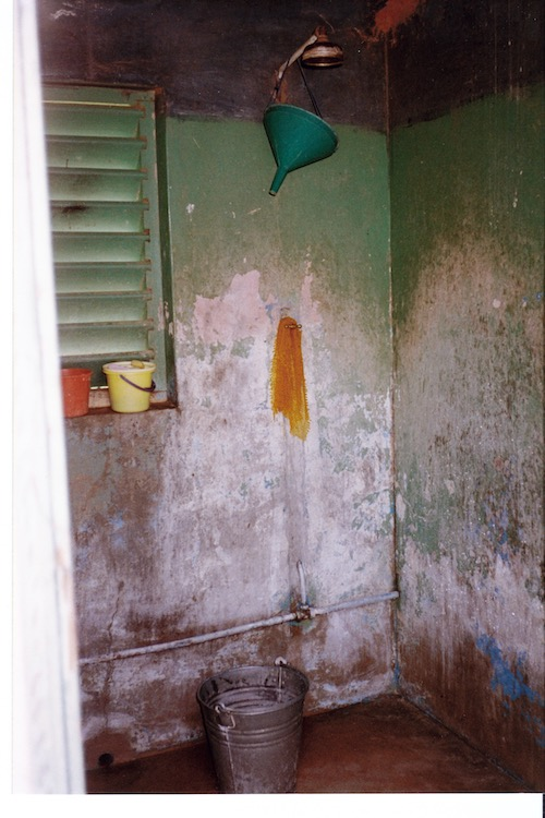 Photo of a corner of a bathing room with a five gallon metal bucket underneath a showerhead. Walls are missing part of their green paint.