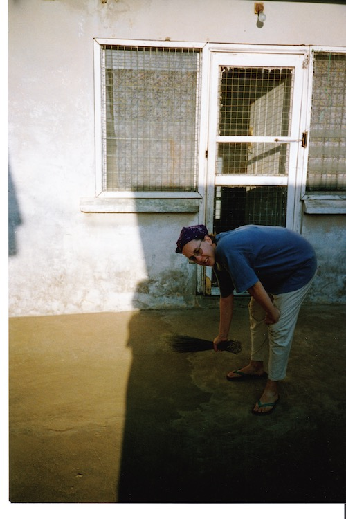 Photo of a courtyard with the left half in the sun and the right half in shade. Vanessa Kier is bent over, holding a short rush broom as she sweeps.
