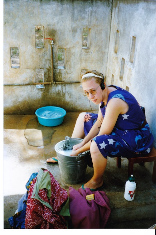 Photo of Vanessa Kier looking less than thrilled while sitting on a stool washing clothes in a five gallon bucket in the washing area by her outdoor faucet.