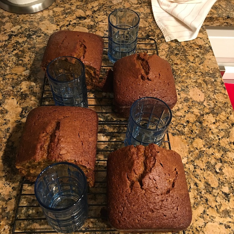 Photo of two loaves of pumpkin bread, cut into halves, on cooling racks. Blue juice glasses sit next to each half.