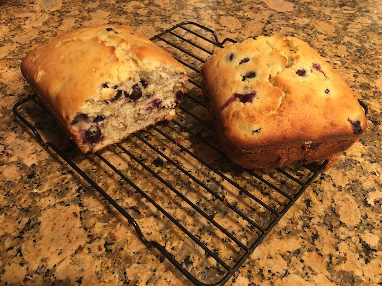Photo of a loaf of lemon blueberry bread cut in half, sitting on a wire cooling rack.